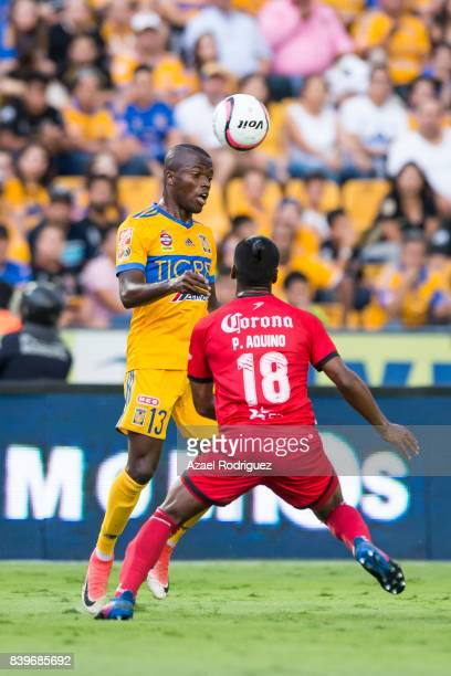 Enner Valencia of Tigres heads the ball over Pedro Aquino of Lobos during the seventh round match between Tigres UANL and Lobos BUAP as part of the...