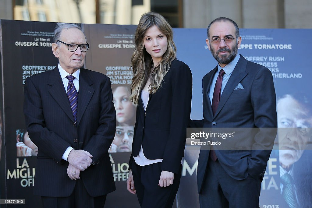 <a gi-track='captionPersonalityLinkClicked' href=/galleries/search?phrase=Ennio+Morricone&family=editorial&specificpeople=677347 ng-click='$event.stopPropagation()'>Ennio Morricone</a>, Sylvia Hoeks and <a gi-track='captionPersonalityLinkClicked' href=/galleries/search?phrase=Giuseppe+Tornatore&family=editorial&specificpeople=2761023 ng-click='$event.stopPropagation()'>Giuseppe Tornatore</a> attend the 'La Migliore Offerta' photocall at The Space Moderno on December 28, 2012 in Rome, Italy.