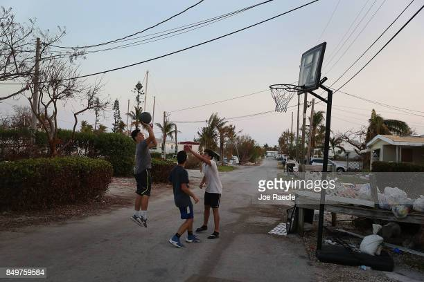 Enoc Campos Jimmy Gimeranes and Mathias Trujillo play basketball as they take a break from cleaning up a home that was damaged by hurricane Irma on...