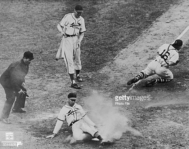 Enos Slaughter of the St Louis Cardinals slides into home as catcher Roy Partee of the Boston Red Sox goes up the third base line to retrieve the...