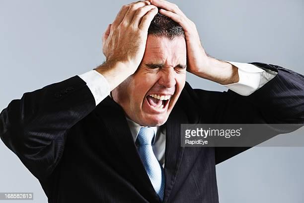Enough! Desperate businessman clutches his head and screams
