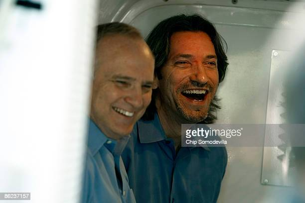 Enough Project cofounder and human rights activist John Prendergast and Rabbi David Saperstein laugh in the back of a police van after being arrested...