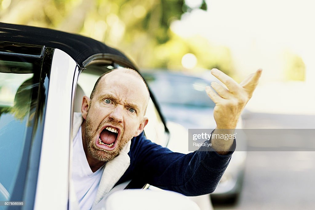 Enraged male driver shouts and gestures threateningly : Stock Photo