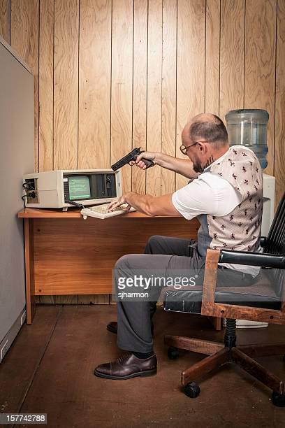 enraged office working aiming gun at old broken computer