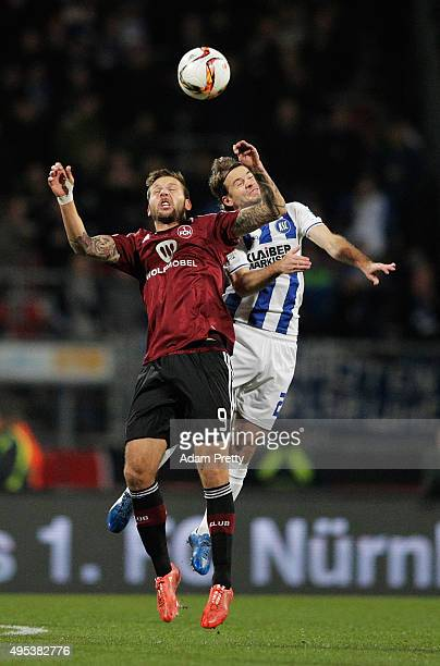 Enrico Valentini of Karlsruher SC is challenged by Guido Burgstaller of 1FC Nurnberg during the 2 Bundesliga match between 1 FC Nuernberg and...