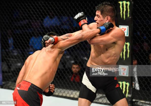 Enrique Barzola punches Gabriel Benitez in their featherweight fight during the UFC 211 event at the American Airlines Center on May 13 2017 in...