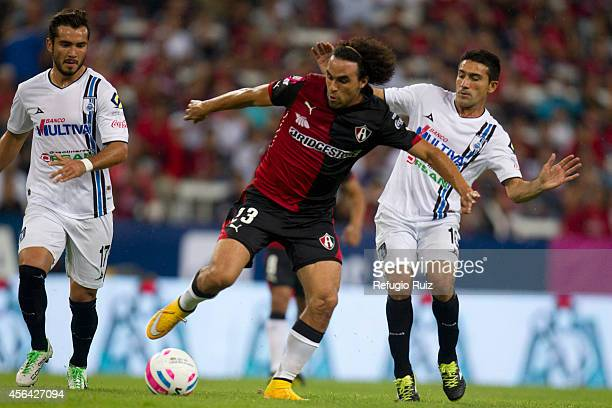 Enrique Esqueda of Atlas fights for the ball with Antonio Naelson of Queretaro during a match between Atlas and Queretaro as part of 11th round...