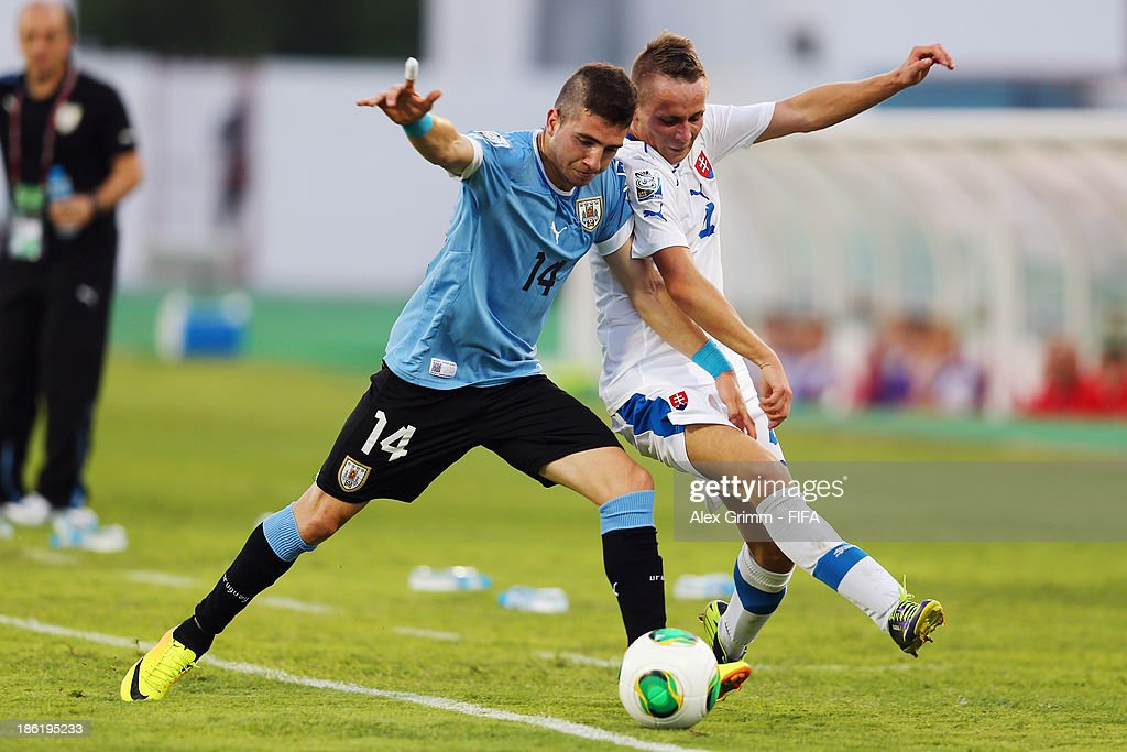 Enrique Etcheverry (L) of Uruguay is challenged by Martin Slaninka of Slovakia during the FIFA U-17 World Cup UAE 2013 Round of 16 match between Uruguay and Slovakia at Ras Al Khaimah Stadium on October 29, 2013 in Ras al Khaimah, United Arab Emirates.