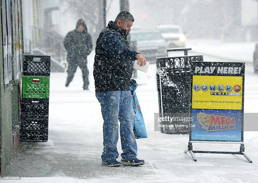 Enrique Gonzalez, an employee for Rodriguez Grocery, spreads rock salt after shoveling the sidewalk on Wednesday, December 26, 2012, in Allentown, Morning Call.