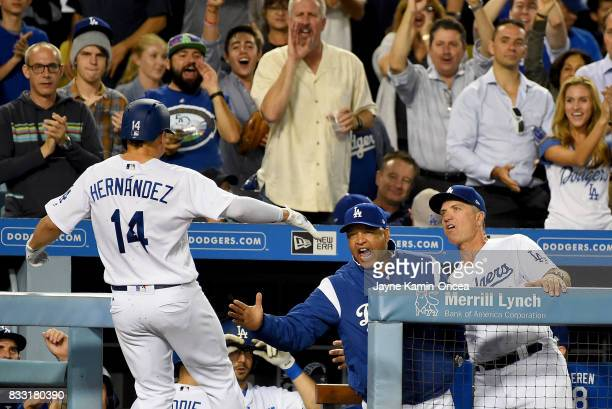 Enrique Hernandez of the Los Angeles Dodgers is greeted in the dugout by manager Dave Roberts and coach Bob Geren after a solo home run in the fourth...