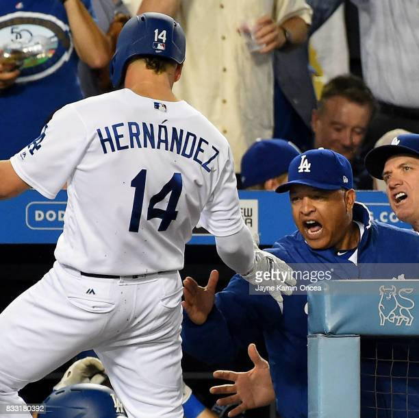 Enrique Hernandez of the Los Angeles Dodgers is greeted in the dugout by manager Dave Roberts after a solo home run in the fourth inning of the game...