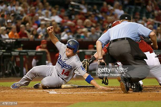 Enrique Hernandez of the Los Angeles Dodgers safely slides in to score a run past the tag from catcher Jarrod Saltalamacchia of the Arizona...