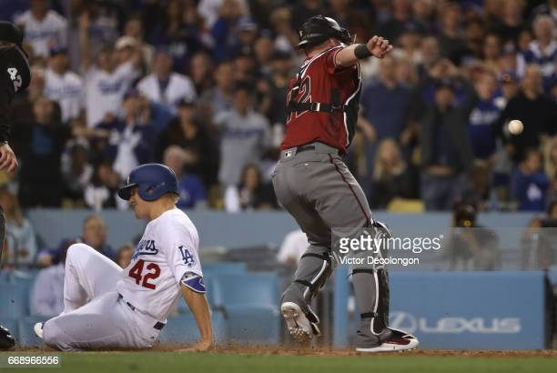 Enrique Hernandez of the Los Angeles Dodgers scores on a throwing error to third base by catcher Chris Hermann of the Arizona Diamondbacks in the...