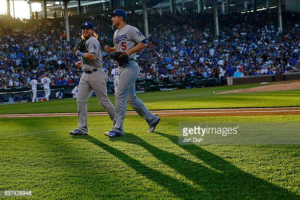 Enrique Hernandez of the Los Angeles Dodgers smiles as he walks to the dugout with Corey Seager after the end of the first inning against the Chicago...