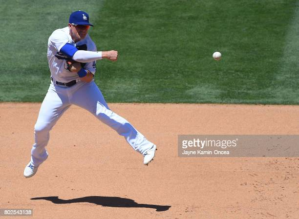 Enrique Hernandez of the Los Angeles Dodgers throws to first from short stop for an out in the game against the Colorado Rockies at Dodger Stadium on...