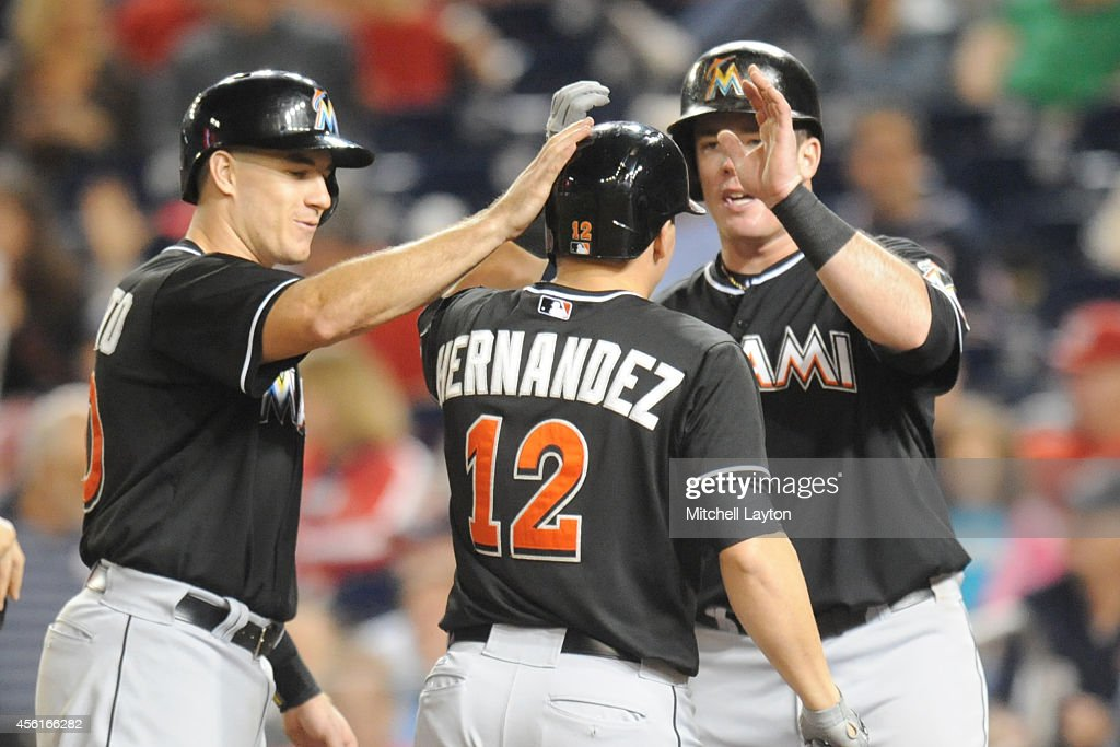 Enrique Hernandez of the Miami Marlins celebrates a three run home run in the eighth inning with Jacob Realmuto and Justin Bour during game two of a...