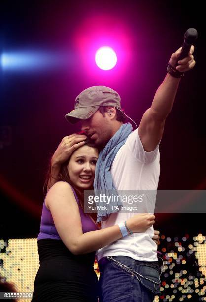 Enrique Iglesias on stage with a member of the crowd during Capital 958 Summertime Ball with Barclaycard at the Emirates Stadium