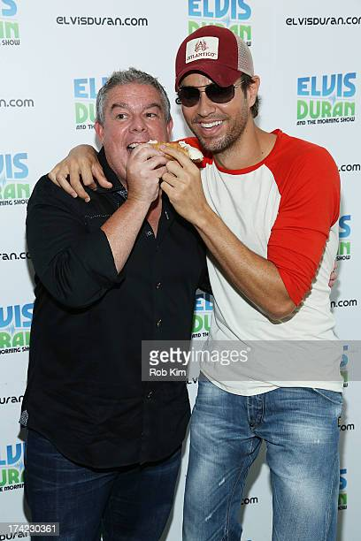 Enrique Iglesias shares a cannoli with host Elvis Duran at 'The Elvis Duran Z100 Morning Show' at Z100 Studio on July 18 2013 in New York City