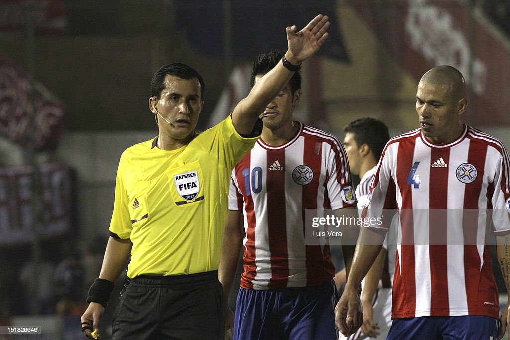 Enrique Osses, FIFA referee, Darío Veron and <a gi-track='captionPersonalityLinkClicked' href=/galleries/search?phrase=Marcelo+Estigarribia&family=editorial&specificpeople=5356243 ng-click='$event.stopPropagation()'>Marcelo Estigarribia</a> of Paraguay reacts during a match between Paraguay and Venezuela as part of the South American Qualifiers for the FIFA Brazil 2014 World Cup at the Estadio Defensores del Chaco on September 11, 2012 in Asunción, Paraguay.
