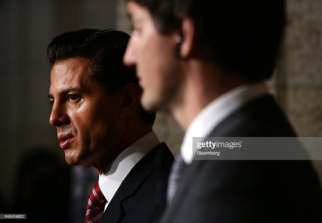 Enrique Pena Nieto, Mexico's president, left, speaks as Justin Trudeau, Canada's prime minister, listens during a joint press conference at Parliament Hill ahead of the North American Leaders Summit (NALS) in Ottawa, Ontario, Canada, on Tuesday, June 28, 2016. Trudeau, Nieto, and U.S. President Barack Obama hold the so-called Three Amigos summit Wednesday in Ottawa, with fallout from the U.K.'s vote last week to leave the European Union raising pressure to show confidence in their own alliance. The countries will vow to produce more clean power and cut methane emissions while strengthening economic ties. Photographer: Cole Burston/Bloomberg via Getty Images