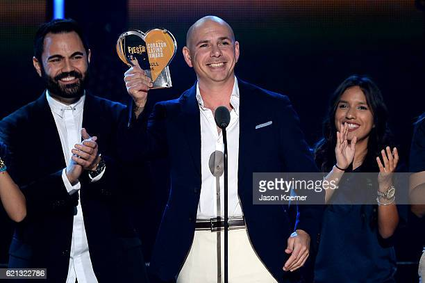 Enrique Santos presents the Fiesta Latina Corazon Latino award to Pitbull on stage at iHeartRadio Fiesta Latina at American Airlines Arena on...