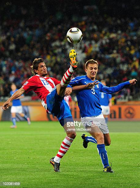 Enrique Vera of Paraguay controls the ball in the air under pressure by Domenico Criscito of Italy during the 2010 FIFA World Cup South Africa Group...