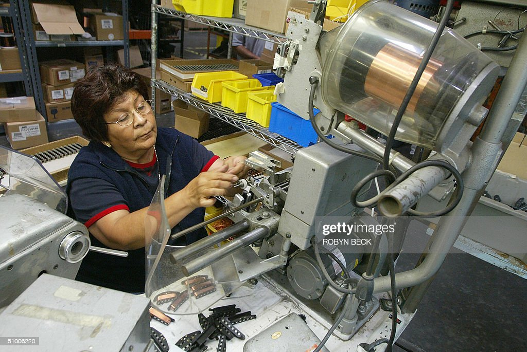 Enriqueta Castillo threads hairthin copper wire onto spools for electric guitar pickups at the Fender manufacturing facility in Corona California 28...