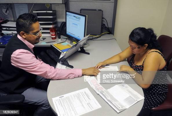 Enrollment Specialist Horacio Castaneda left helps Rosa Ayala Cruz right apply for health benefits at the Denver Health Westside Family Health Center...