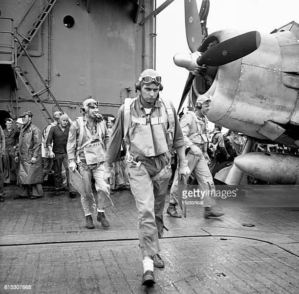 Ensign Charles Miller Lt Henry Dearing and Lt Bus Alber of Air Squadron 12 walk to their planes aboard the USS Saratoga They are headed for a bombing...