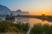 Sunrise inside the Entabeni Game Reserve famous for safari with a reflection of the Hanging Lip of Hanglip mountain peak in a swamp lake located near Kruger Park, Limpopo Province, South Africa.