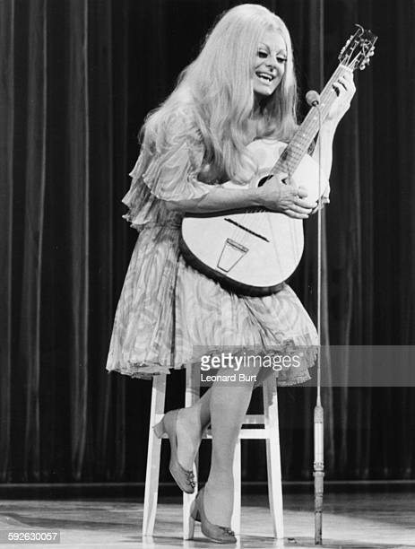 Entertainer and drag artist Danny la Rue impersonating pop singer Mary Hopkins wearing a long blonde wig and playing the guitar during rehearsals for...