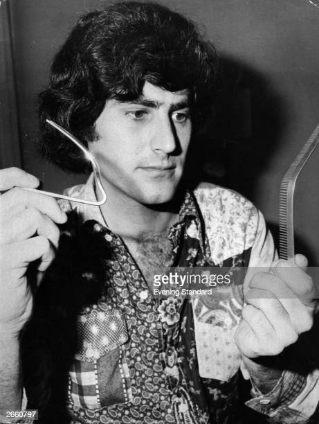 Entertainer and exponent of the paranormal Uri Geller holds some metal objects bent in his famous act