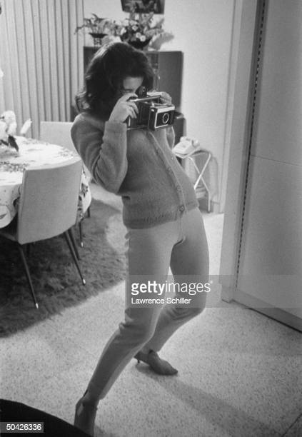 Entertainer AnnMargret slouching down to take picture w Polaroid camera indoors