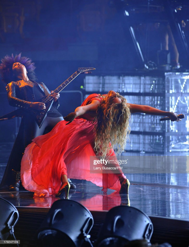Entertainer Beyonce performs on stage during 'The Mrs. Carter Show World Tour' at the American Airlines Arena on July 10, 2013 in Miami, Florida. Beyonce wore a long red chiffon dress with gold neck hardware by Alon Livne, Stuart Weitzman shoes and hosiery by Capezio.