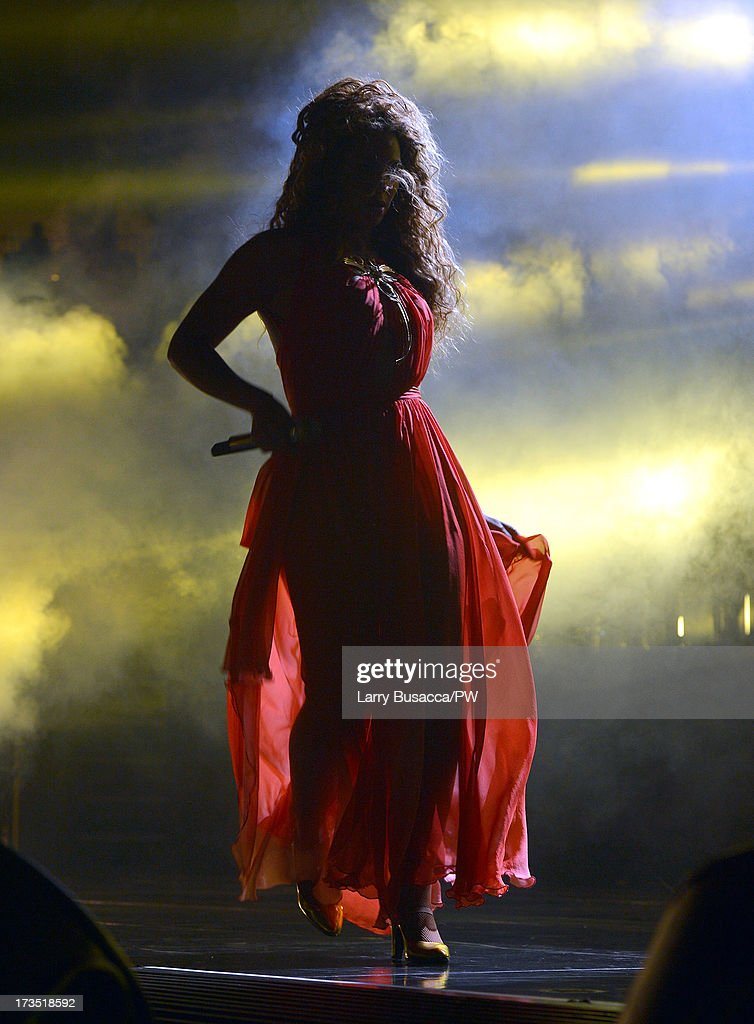 Entertainer Beyonce performs on stage during 'The Mrs. Carter Show World Tour' at the Toyota Center on July 15, 2013 in Houston, Texas. Beyonce wears a long red chiffon dress with gold neck hardware by Alon Livne, Stuart Weitzman shoes and hosiery by Capezio.