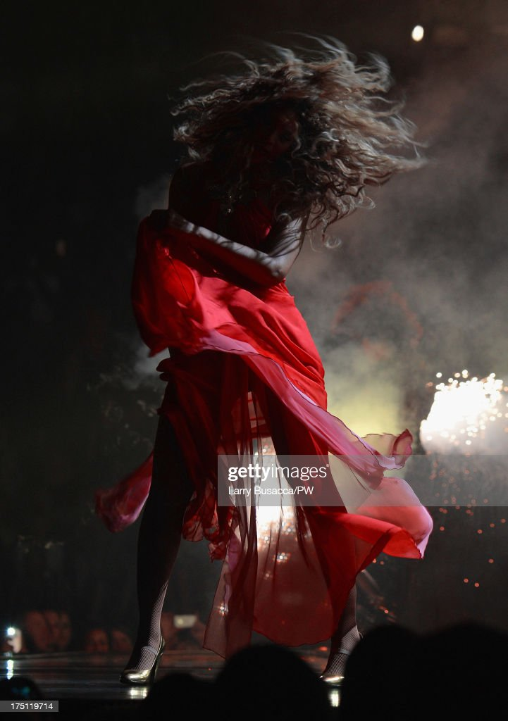 Entertainer Beyonce performs on stage during 'The Mrs. Carter Show World Tour' at the Izod Center on July 31, 2013 in East Rutherford, New Jersey. Beyonce wears a long red chiffon dress with gold neck hardware by Alon Livne, Stuart Weitzman shoes and hosiery by Capezio.