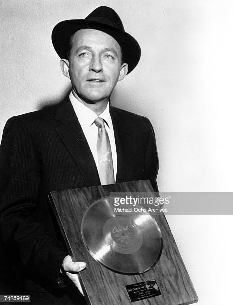 Entertainer Bing Crosby holds a platinum record as he poses for a portrait to commemorate 'one million copies' sold of the song 'True Love' recorded...