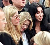 Entertainer Cher her daughter Chastity and Mary Bono the widow of Sonny Bono mourn as Bono's casket is placed inside the hearse after a Catholic...