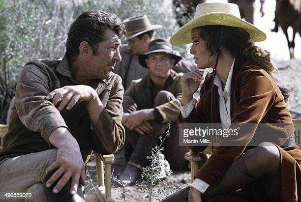 Entertainer Dean Martin and actress Raquel Welch chat on the set of the 20th Century Fox film 'Bandolero' in 1967
