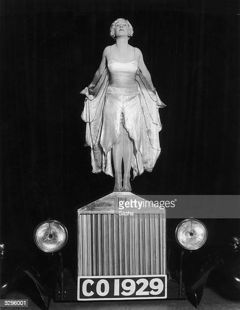 Entertainer Elsa McFarlane stands on the bonnet of a Rolls Royce car mimicking the Silver Lady figurine in a production of 'The CoOptimists' at the...