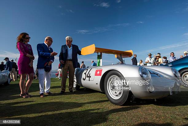 Entertainer Jay Leno right talks with attendees Ugo Gussali Beretta center and Maura Frosia in front of a 1955 Porsche AG 550 RS Spyder vehicle...