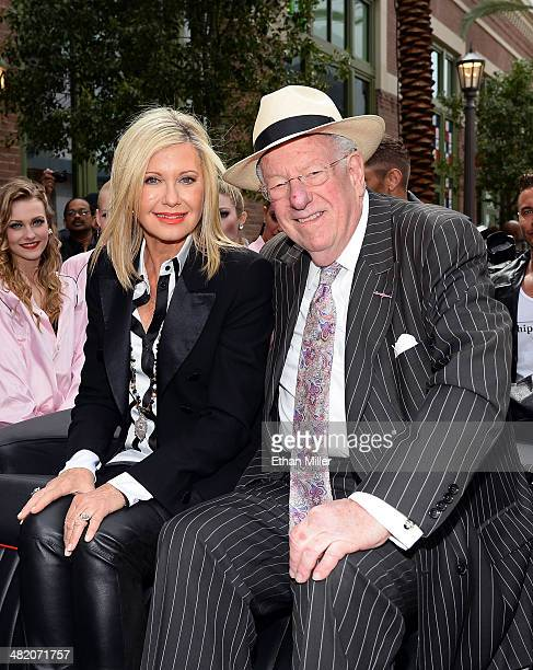 Entertainer Olivia NewtonJohn and Chairman of the Las Vegas Host Committee Oscar Goodman pose in the 'Hell's Chariot' Ford Mercury convertible from...