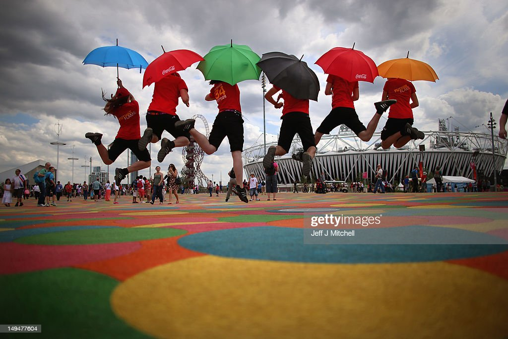 Entertainers jump with umbrellas as members of the public arrive on day one of the London 2012 Olympic Games at the Olympic Park on July 28, 2012 in London, England.