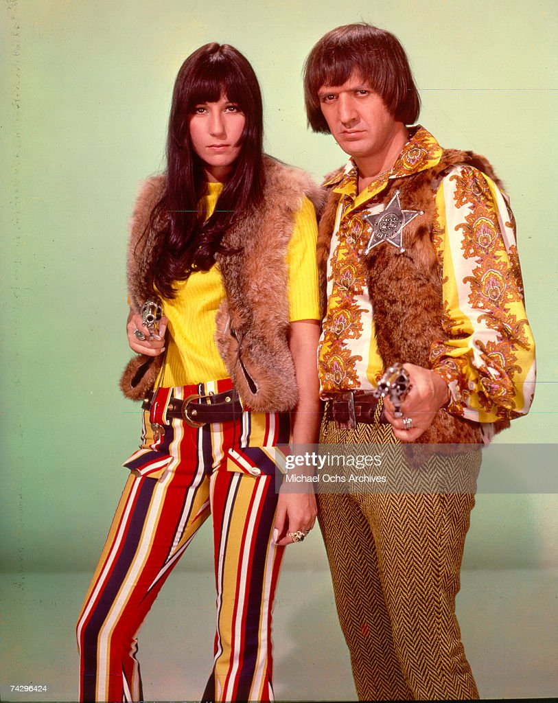 Entertainers Sonny Bono Cher point guns toward the camera as they pose for a portrait in circa 1968