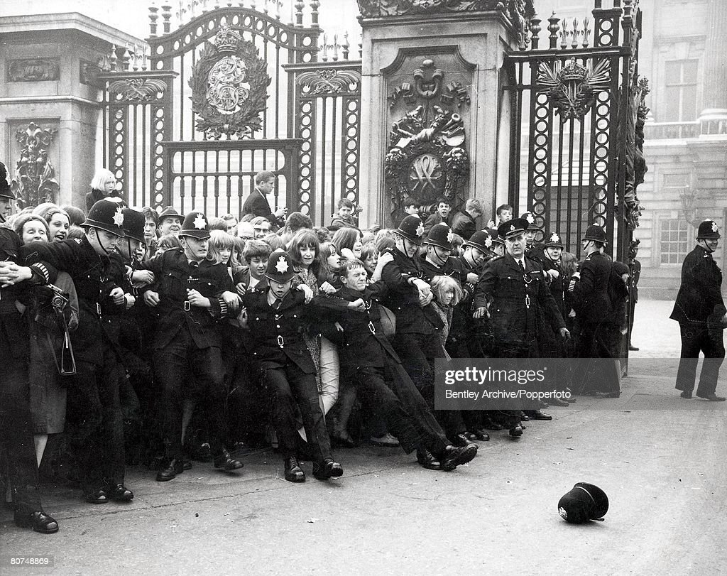 Entertainment, Music, Buckingham Palace, London, 26th October 1965, A Police helmet lies on the ground where it fell, Behind it a line of policemen strain to hold back hundreds of screaming Beatles fans, as they receive their MBEs at Buckingham Palace