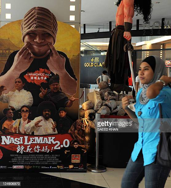 STORY 'EntertainmentMalaysiafilmmusicpoliticsraceFOCUS' by Phil Hazlewood A woman walks past a poster advertising a new movie named after a national...