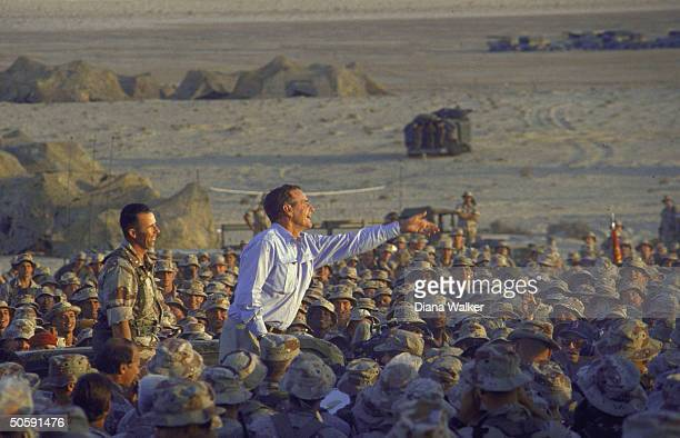 Enthused Pres Bush tossing souvenir tie clips perching above girding crowd of Amer soldiers on USled allied gulf crisis desert duty in Saudi Arabia