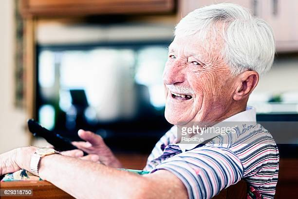 Enthusiastic 90-year-old man choosing TV channel looks round smiling