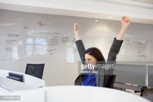 Enthusiastic businesswoman with arms raised in office : Stock Photo