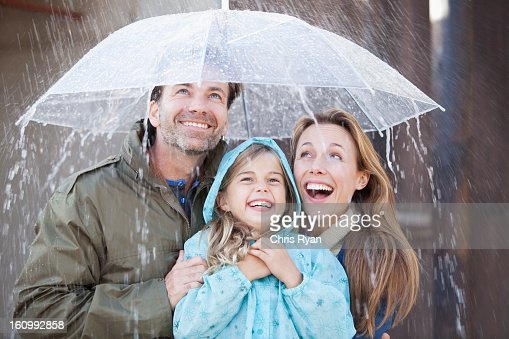 Enthusiastic family under umbrella in downpour
